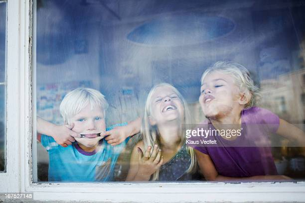 Children making funny faces behind windows