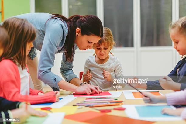 Children making origami in a preschool