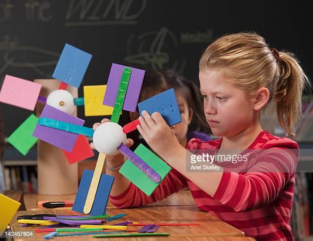 Children making paper wind turbines in classroom