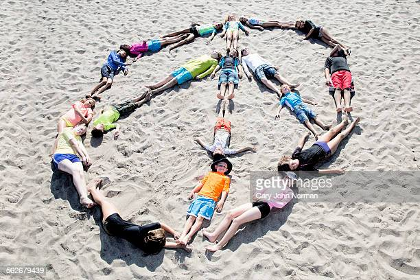 Children making peace sign by laying on the beach