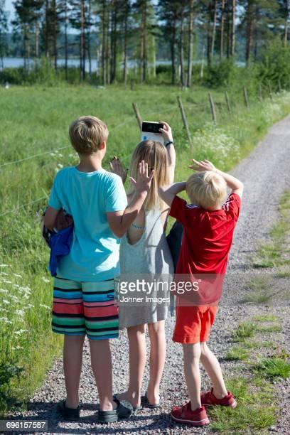 children making selfie on dirt road - レクサンド ストックフォトと画像