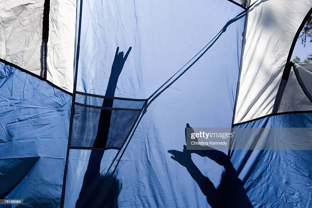 Children making shadow puppets behind a tent : Stock Photo