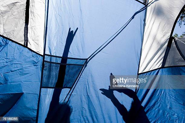 Children making shadow puppets behind a tent