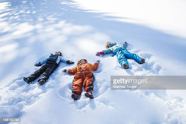 Children making snow angels in a trees shadow
