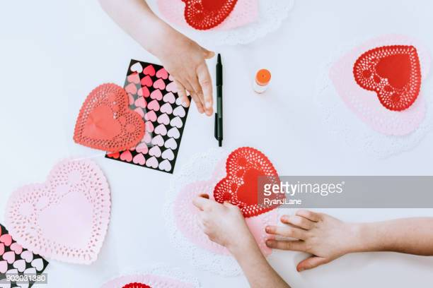 children making valentine's day cards - doily stock photos and pictures