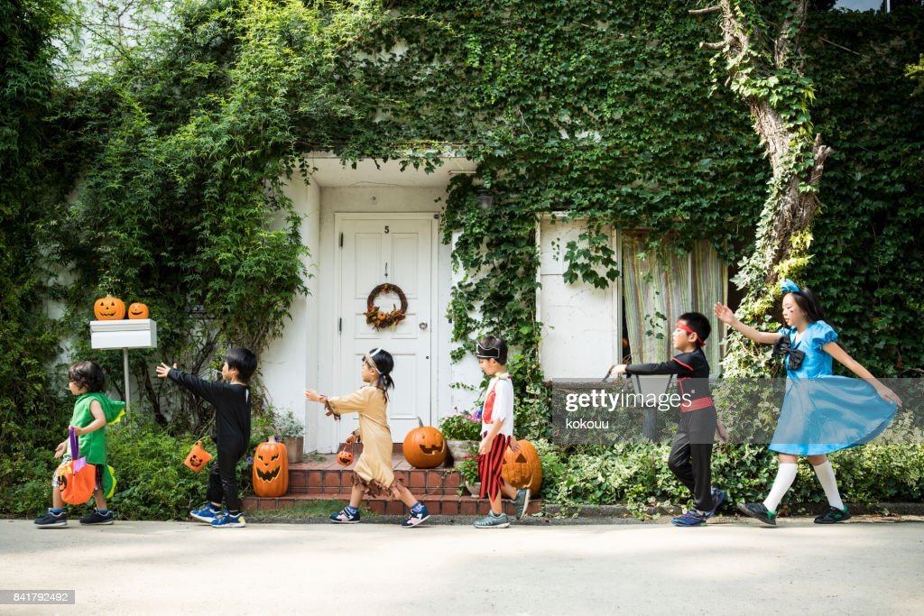 Children marching in front of the house wearing costumes. : Stock Photo