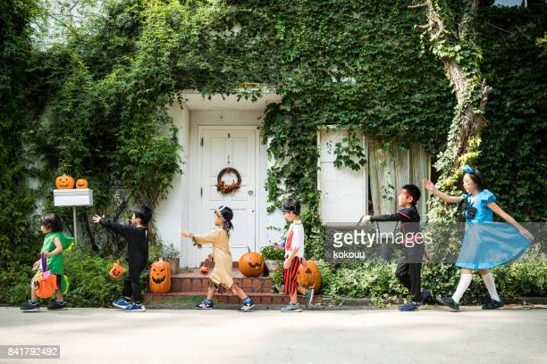 children marching in front of the house wearing costumes. - halloween kids stock photos and pictures