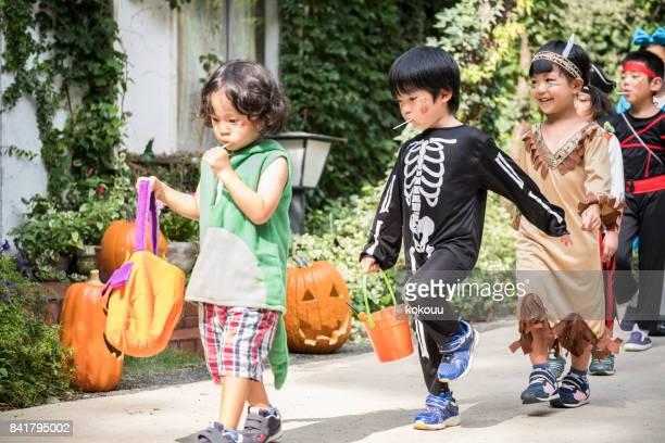 子供たちの衣装を着て家の前に行進しています。