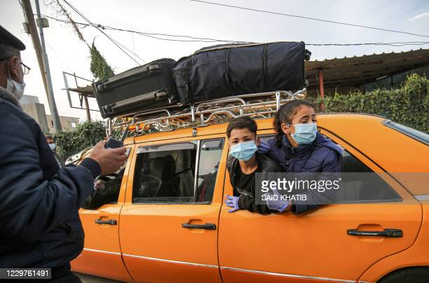 TOPSHOT Children maskclad due to the COVID19 coronavirus pandemic look out from the window of a vehicle transporting Palestinians about to cross onto...