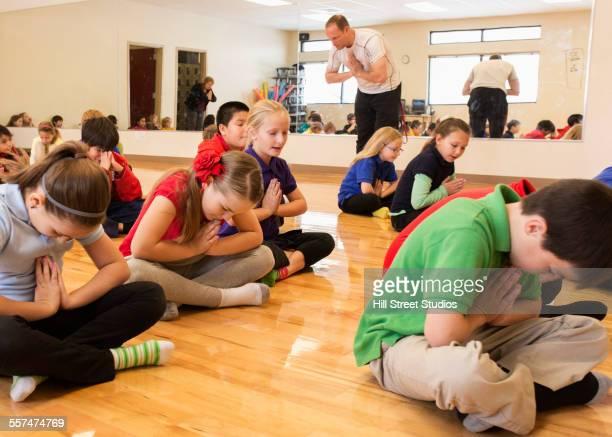 Children meditating in gym class