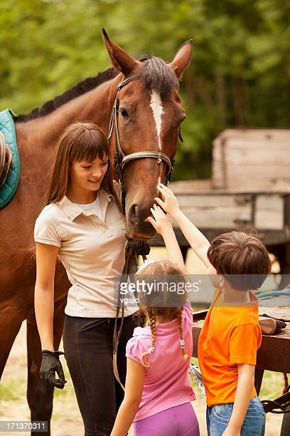 children meeting with horses. - recreational horseback riding stock pictures, royalty-free photos & images
