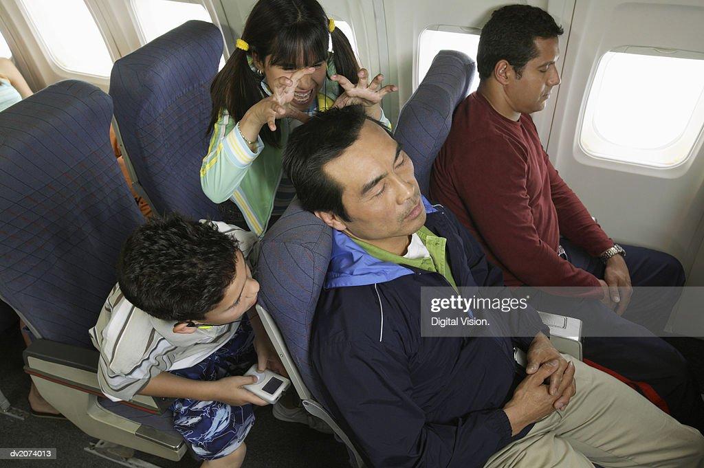 Children Mucking Around Behind a Man on a Plane : Stock Photo