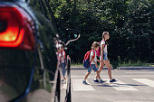 Children next to a car walking through pedestrian crossing to the school