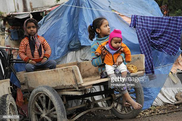 Children of a homeless family play by their roadside shanty during a cold and foggy day on January 3 2015 in Noida India Delhi NCR has a homeless...