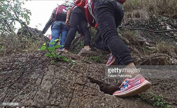 Children of Atule'er Village climb a cliff on their way home in Zhaojue county in southwest China's Sichuan province on May 14 2016 in Zhaojue China...