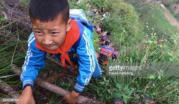 Children of Atule'er Village climb the vine ladder on a cliff on their way home in Zhaojue county in southwest China's Sichuan province on May 14...