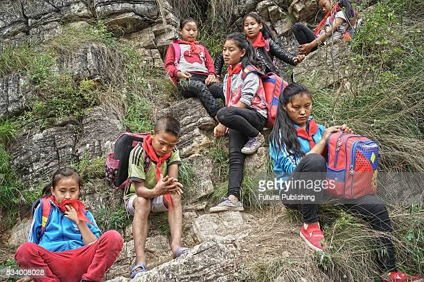 Children of Atule'er Village take a rest during climbing the cliff on their way home in Zhaojue county in southwest China's Sichuan province on May...