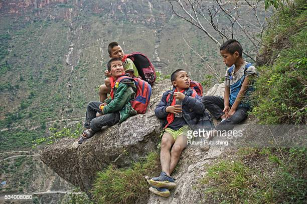 Children of Atule'er Village take a rest during climbing the cliff on their way home in Zhaojue county on May 14 2016 in Zhaojue China There are 17...
