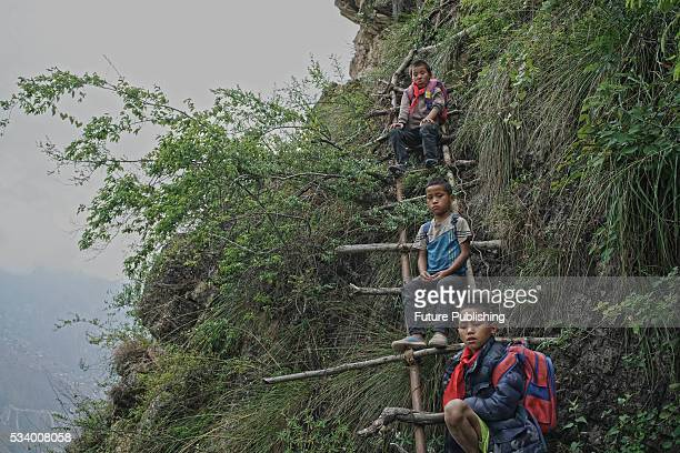 Children of Atule'er Village take a rest during climbing the vine ladder on a cliff on their way home in Zhaojue county in southwest China's Sichuan...