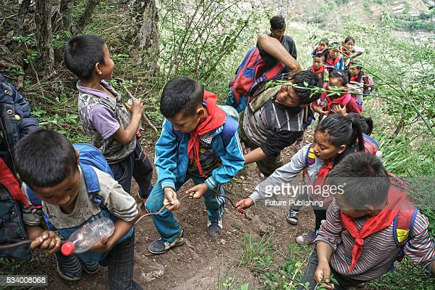 Children of Atule'er Village walk in a queue on their way home in Zhaojue county in southwest China's Sichuan province on May 14 2016 in Zhaojue...