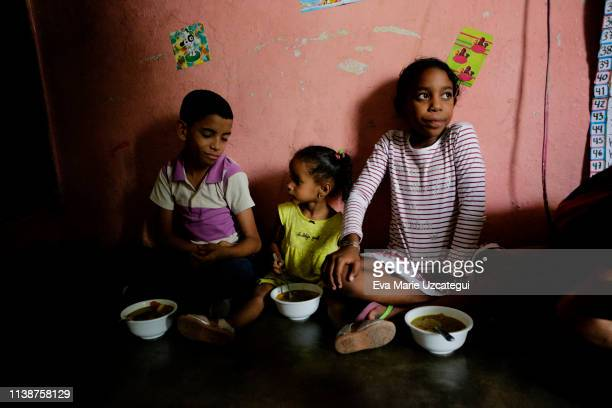 Children of Barrio Unión Sector Las Casitas eat soup prepared and donated by Alto Restaurant in the house of a neighbor on April 12 2019 in Caracas...