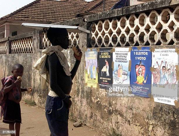 Children of Bissau look at electoral campaign posters 24 March 2004 in Bissau GuineaBissau GuineanBissau will vote for legislative elections 28 March...