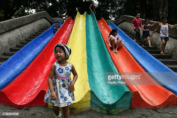 Children of different ages play on the slide not minding the rain at the Children's Playground in Rizal Park Manila This year's Father's Day is...
