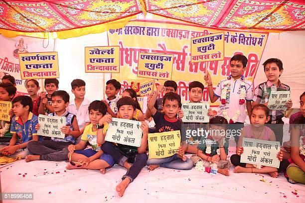 "Children of Jewelers association members and workers holding banner with written slogan ""Father on Strike, Pay School fess Modi Uncle"" during a..."