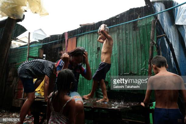 Children of land grabbing victims of Borei Keila area washing hair by a heavy rain at the evictees camp
