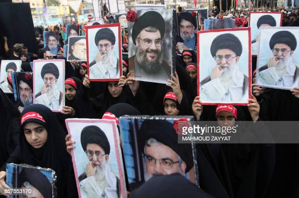 Children of members of Lebanon's Shiite Hezbollah movement hold portraits of Hezbollah chief Hasan Nasrallah and Iran's supreme leader Ayatollah Ali...