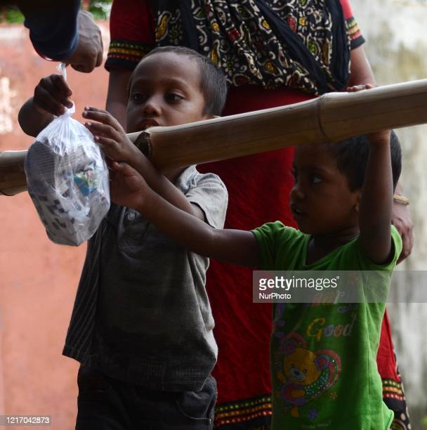 Children of Migrant labourer collects food during the waiting for a bus to go their native place return from Maharashtra by train in Barasat,...