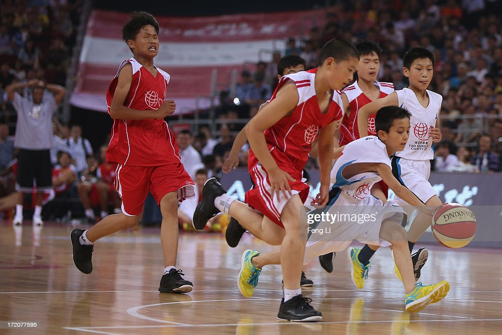 Children of migrant workers complete the ball during the 2013 Yao Foundation Charity Game between China team and the NBA Stars team on July 1, 2013 in Beijing, China.