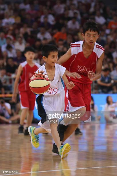 Children of migrant workers complete the ball during the 2013 Yao Foundation Charity Game between China team and the NBA Stars team on July 1 2013 in...