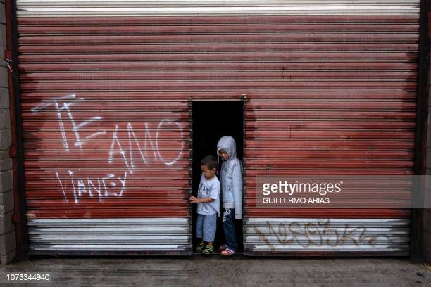 Children of migrants travelling in the Central American caravan hoping to reach the United States are seen at the entrance of a warehouse now being...