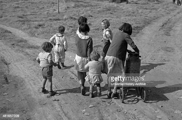 Children of migratory workers, hauling water, American River camp, San Joaquin Valley, California by Dorothea Lange 1895-1965, dated 19360101