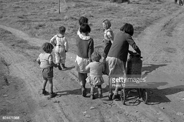 Children of migratory workers, hauling water, American River camp, San Joaquin Valley, California by Dorothea Lange 1895-1965, dated 1936.