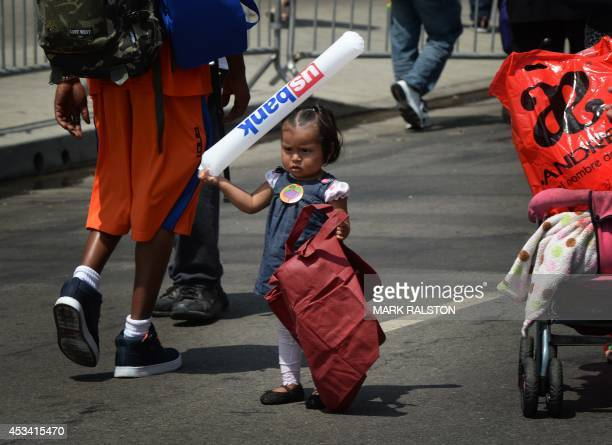 Children of poor migrant families receive backpacks filled with school supplies before the start of the new school year during a charity event at the...