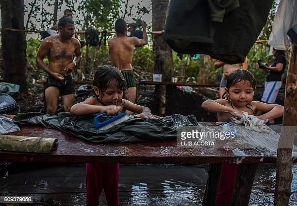 TOPSHOT Children of Revolutionary Armed Forces of Colombia Members wash clothes at the camp in Llanos del Yari Caqueta department Colombia on...