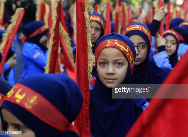 Children of supporters of the Lebanese Shiite Hezbollah movement take part in a mourning procession on the tenth day of the lunar month of Muharram,...