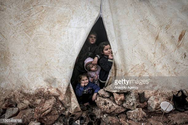 Children of Syrian families, who have been forcibly displaced due to the ongoing attacks carried out by Assad regime and its allies, look out of a...
