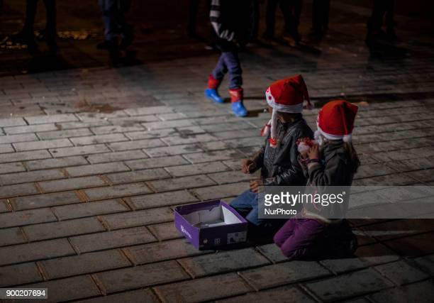 Children of Syrian refugees wearing a Santa Claus hat sitting in the middle of the street to beg during the New Year 2018