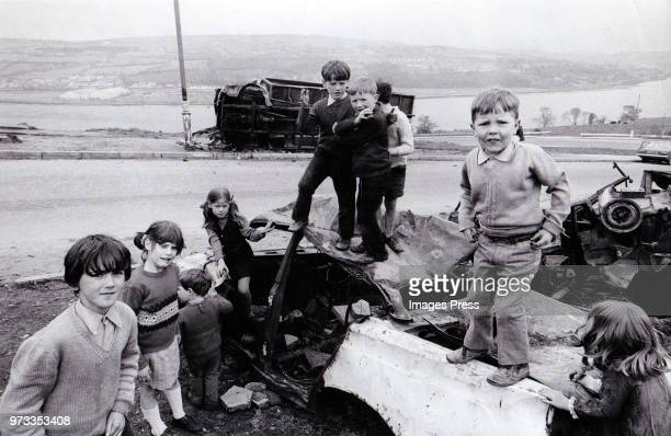 Children of the Catholic area in Londonderry play on burnt out automobiles circa 1972 in Northern Ireland.