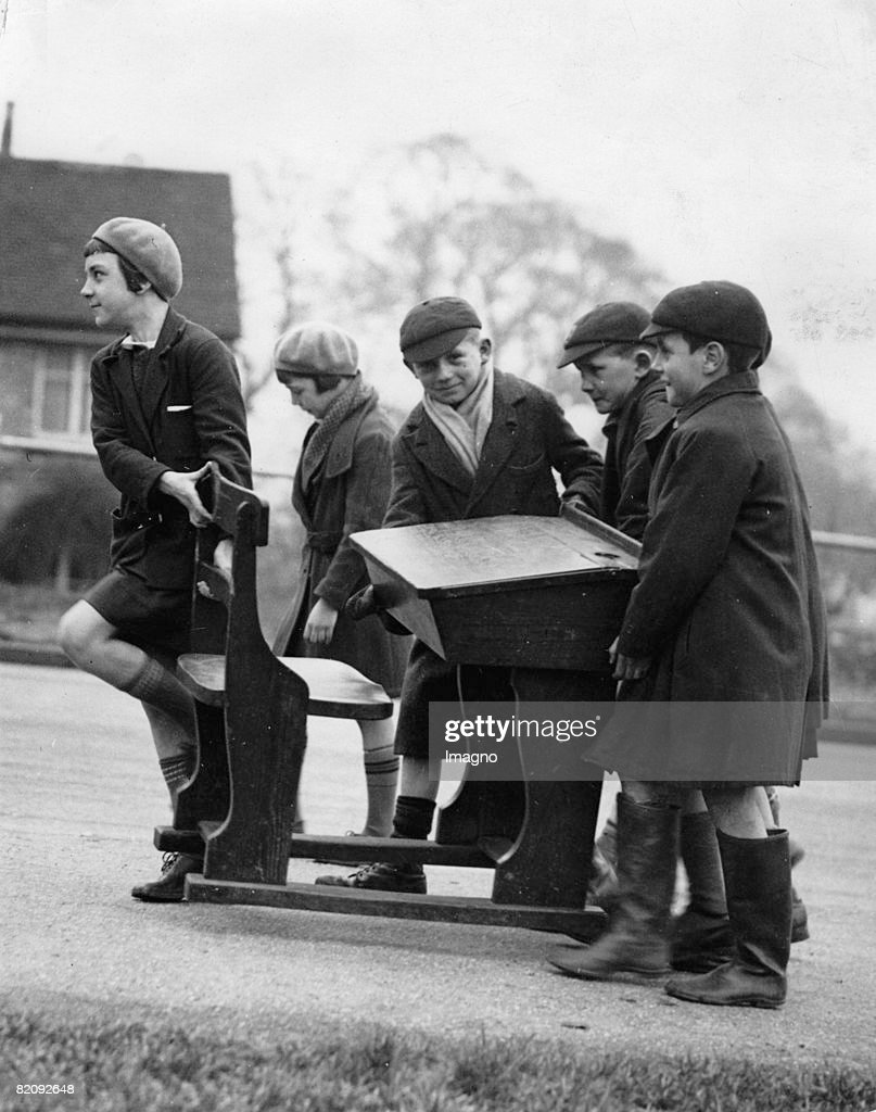 Children of the Loughton Council School have the opportunity to buy their old school desks, Five children carrying home a desk, Photograph, England, 5th March 1935 : News Photo