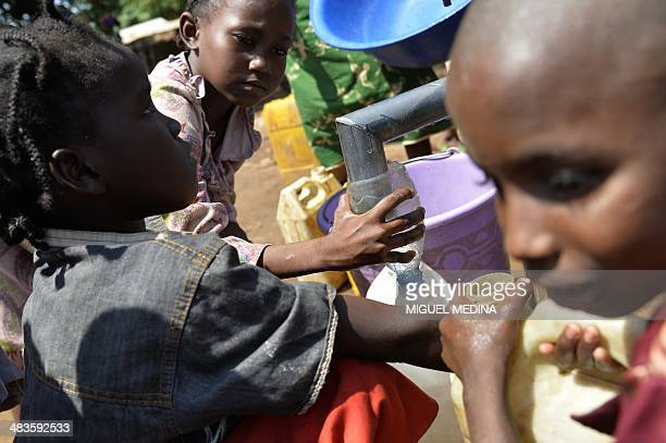 Children of the Pulaar ethnicity fill bottles with water in the Begoua district northeast of Bangui during a humanitarianmedical assistance event on...