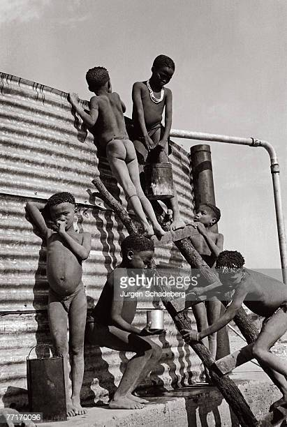 Children of the San tribe of Kalahari bushmen collect water from a borehole at Lonetree Pan Botswana 1959