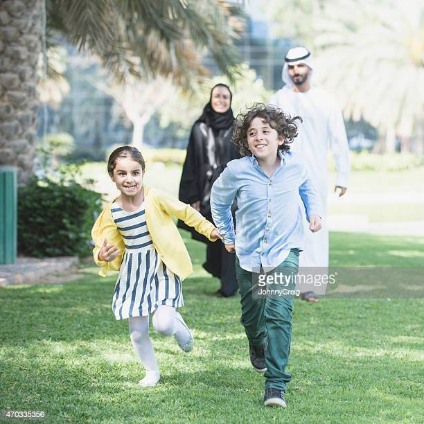 Children of traditional Arab family run through park