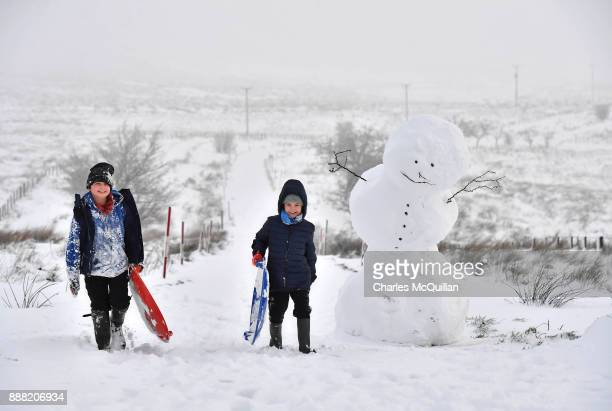 Children off from school due to the weather make their way past a large snowman on Black mountain on December 8 2017 in Belfast Northern Ireland The...