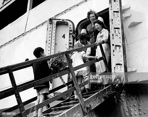 Children offering bouquets of flowers from their gardens to the nurses and injured soldiers a board the hospital ship docked at Avonmouth. May 1945...