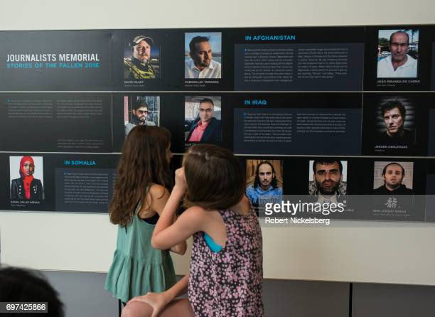 Children on a school trip to the Newseum look at a memorial display of photographs and descriptions of journalists killed around the world in 2016 in...