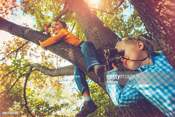 Kinder auf dem Baum im Herbst